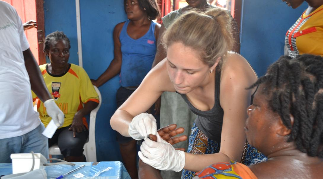 A volunteer takes a blood sample in Ghana to a pregnant woman during her midwifery internship with Projects Abroad.